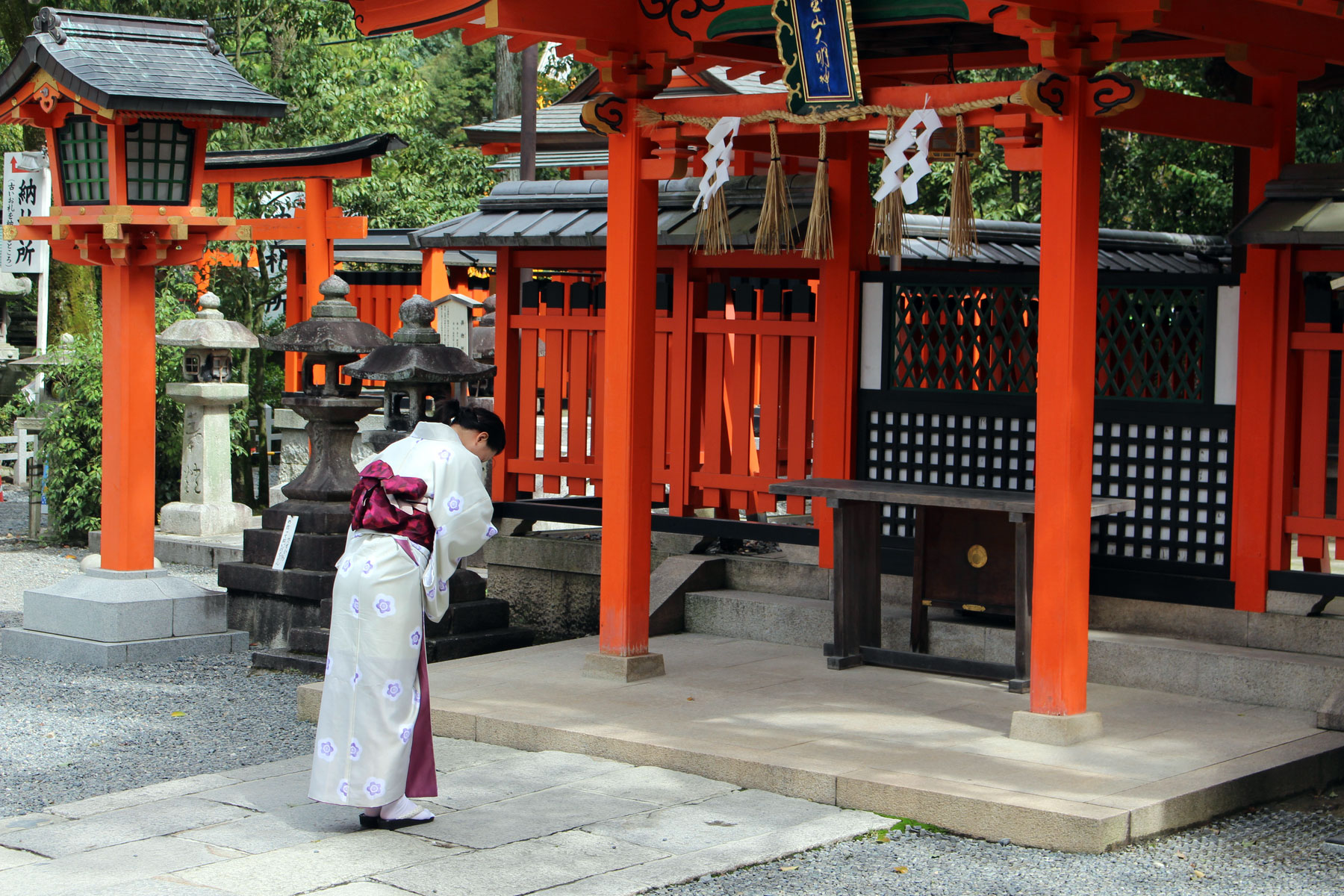 Woman in a kimono bowing in prayer at Fushimi Inari Shrine in Kyoto, Japan