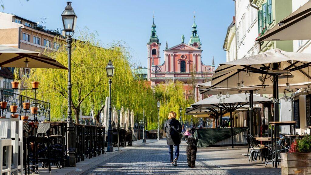 A lady walks her dog down empty streets in Ljubljana</em>